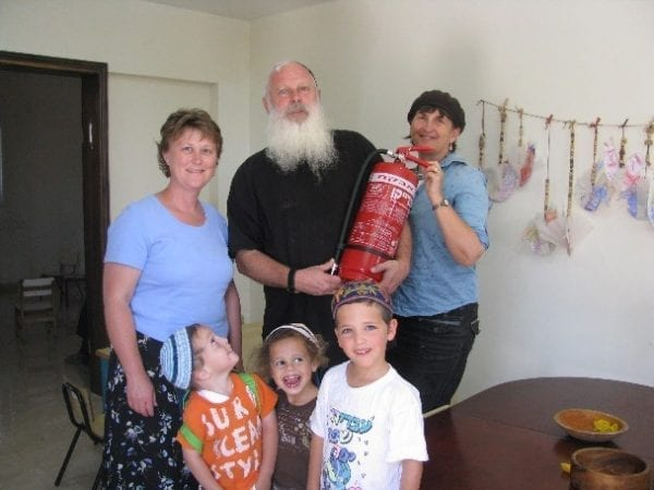 Sondra Baras and a man holding a fire extinguisher. Also in the picture Kim troup and 3 kids